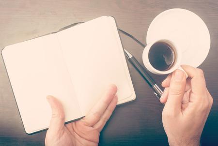 Man überprüft sein Notizbuch und trinkt seinen Kaffee, im Retro-Look Standard-Bild - 43355049