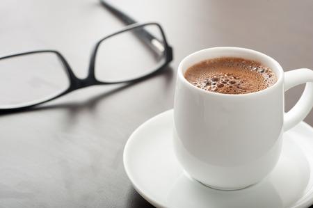 Schließen Sie oben von einer Schale coffe mit Augengläsern auf Couchtisch Standard-Bild - 43354896