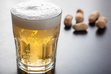 Nahaufnahme von einem Glas Lagerbier und Muttern Standard-Bild - 43354919