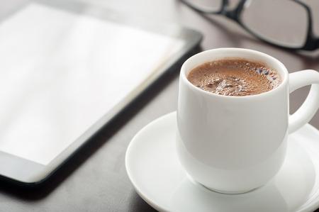 Schließen Sie oben von einer Tasse Kaffee auf Schreibtisch mit einem Tablet-Gerät und Brillen Standard-Bild - 43354803