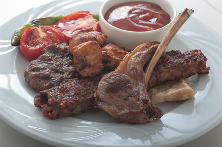 consisting: Close up of a plate of Turkish style mixed kebap, consisting of lamb chops, meat balls, chicken and adana kebap served with grilled tomatoes and green peppers