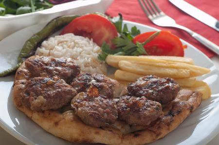 Traditionelle türkische gegrillte Fleischbällchen serviert mit Reis, gebratene Chips, Fladenbrot und gegrillte Paprika und Tomaten Standard-Bild - 43348570