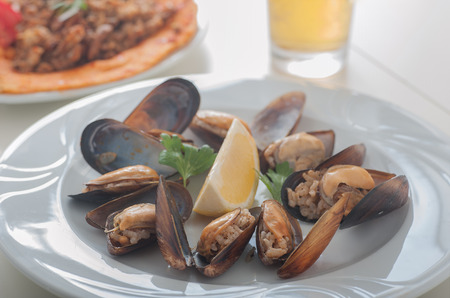 Close up of a plate of Turkish style stuffed mussels called midye dolma with beer