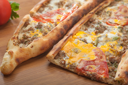 Close up of a delicious crispy Turkish pide made with minced meat, eggs, tomatoes and green peppers 写真素材