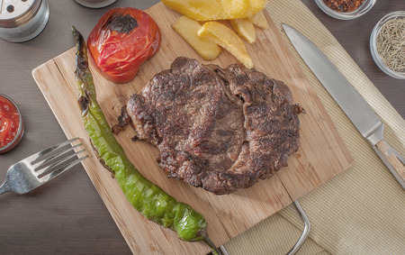 Close up of a grilled beef steak served with grilled tomatoes, peppers and chips, from above. Stok Fotoğraf