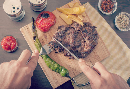 Man cutting and eating a grilled beef steak served with grilled tomatoes, peppers and chips