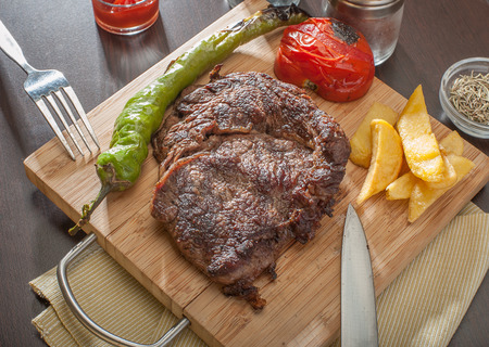 Close up of a grilled beef steak served with grilled tomatoes, peppers and chips.