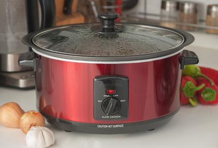 cooking: Cerca de una olla de cocci�n lenta trabajando en estante de la cocina Foto de archivo