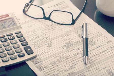 calculadora: Primer plano de un formulario de solicitud de pr�stamo para la vivienda de banco en el escritorio con los vidrios de la calculadora y de los ojos