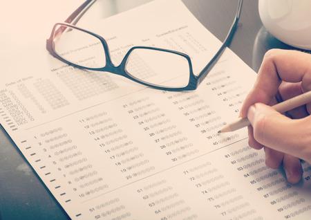 Close-up van een man het invullen van een gestandaardiseerde test vorm Stockfoto