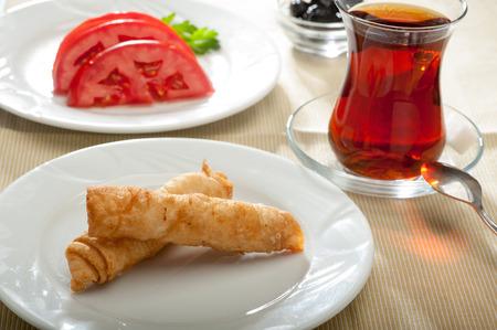 Berühmte türkischen Rollen genannt sigara böre?i, serviert mit Tomaten, schwarzen Oliven und Tee. Standard-Bild - 44397392