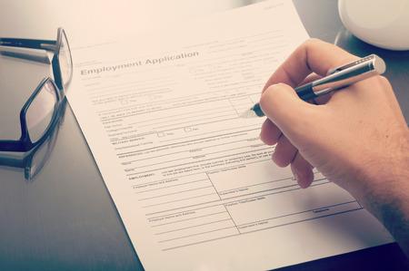 Close up of a man filling a job application form