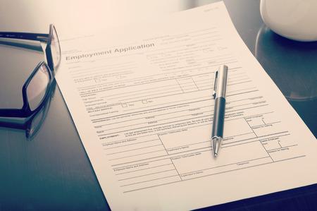 gafas: Cerca de una solicitud de empleo en el escritorio con la pluma y gafas
