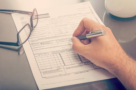 seguro: Cierre plano de un hombre llenando un formulario de reclamación de seguro de salud Foto de archivo