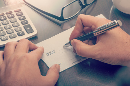 firmando: Hombre que escribe un cheque de pago en la mesa con la calculadora y gafas