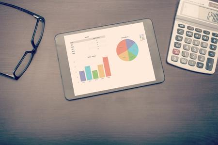 Ein Tablet-Gerät Statistiken über destop mit Brille und Rechner, von oben betrachtet zeigt Standard-Bild - 44512504