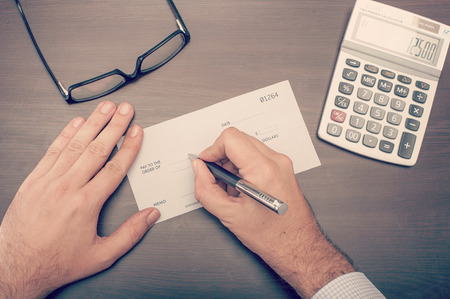 chequera: Hombre que escribe un cheque en su escritorio se ve desde arriba