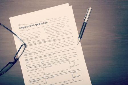 Job application form on desk with pen and glasses viewed from above Stok Fotoğraf