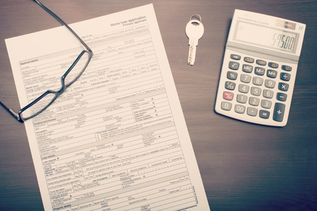 Home loan application form on desk with glasses, key and calculator, viewed from abobve
