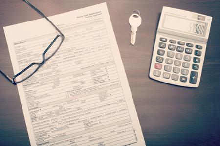 Startseite Darlehen Antragsformular auf dem Schreibtisch mit Brille, Schlüssel und Rechner, gesehen von abobve Standard-Bild - 44512650