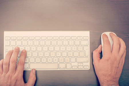 Man using keyboard and mouse at the desktop viewed from above 写真素材