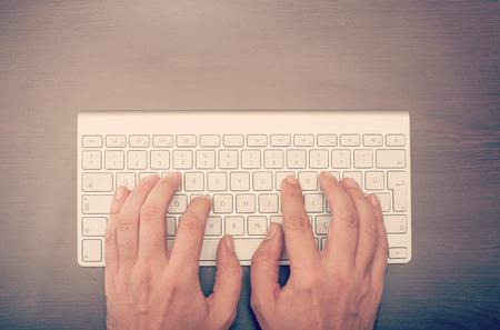 klawiatury: Człowiek wpisując na klawiaturze widziana z góry