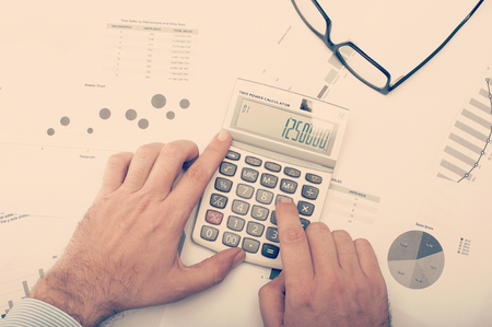 Businessman checking charts and statistics and using calculator on desktop Stok Fotoğraf