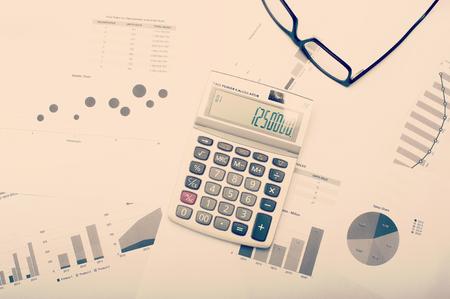 Diagramme und Statistiken auf dem Desktop mit Taschenrechner und Stift, von oben betrachtet. Standard-Bild - 44591385