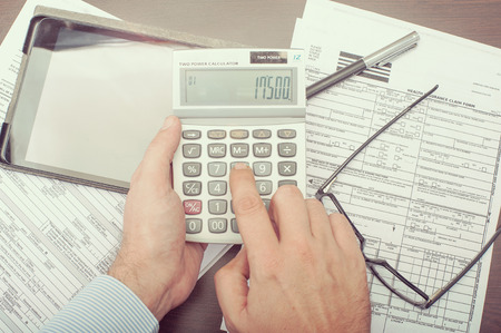 Man calculating his expenses for health insurance claim form
