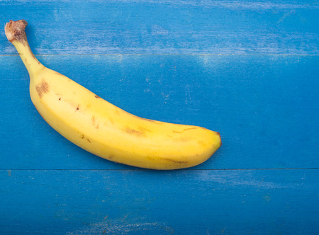 Close up of a single banana on a wooden blue background