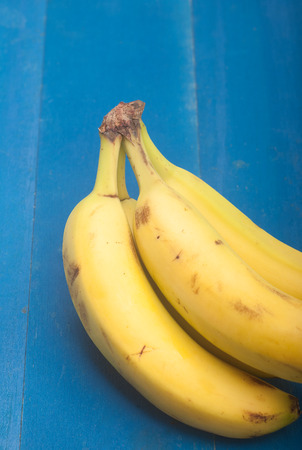 Close up of bananas on wooden blue background