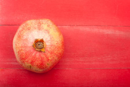 Close up of a pomegranate on a red wooden background viewed from above Stok Fotoğraf