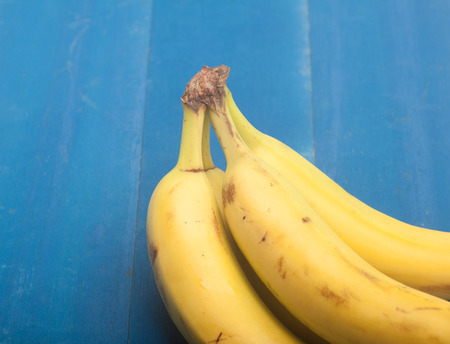 Close up von Bananen auf einem hölzernen blauen Hintergrund Standard-Bild - 49986829