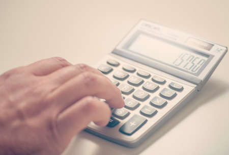 Close up of a businessman using a calculator on desk