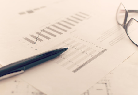 Close up of a business report with charts and diagrams on desktop with pen and glasses
