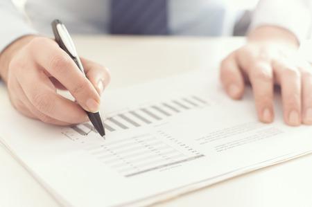Close up von einem Geschäftsmann einen Geschäftsbericht auf Desktop-Überprüfung Standard-Bild - 52879886