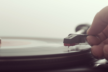 Close up of a man putting a vinly record on turntable 写真素材