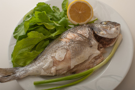Close up of a plate of baked gilthead on plate, served with fresh rocket and onions and lemon. Fish is an healthy alternativeto your daily diet.