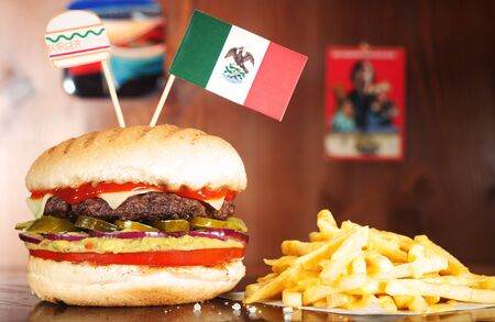 Mexican Hamburger on wooden table served with french fries