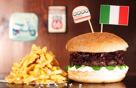 Italian Hamburger on wooden table served with french fries