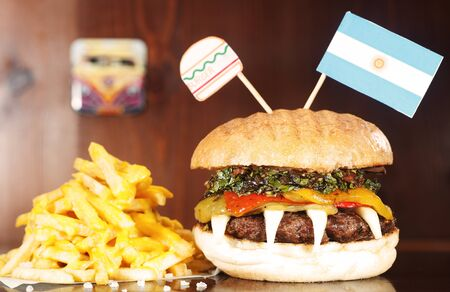 Argentinian Hamburger on wooden table served with french fries 写真素材