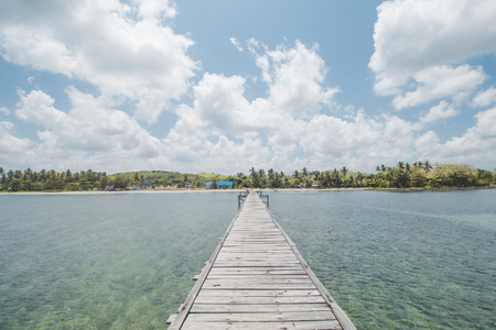 Wooden Dock, Clear Sea Water, Tropical Forest, Cloudy Sky and Tropical Beach