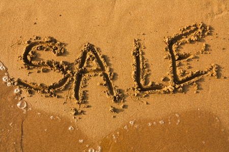 Word Sale on clean sand with water of sea. Sale summer background. photo