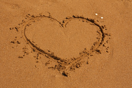 Heart on the sand beach. Conceptual love sea design. Valentine day photo. photo