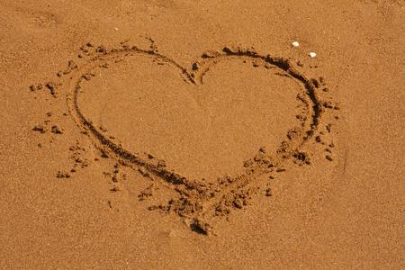 a serene life: Heart on the sand beach. Conceptual love sea design. Valentine day photo.