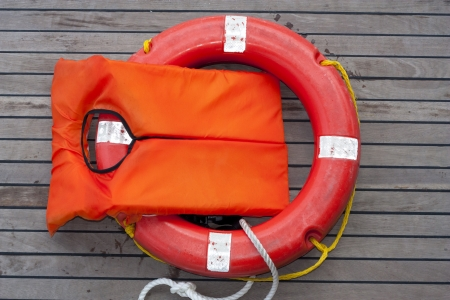Orange life jacket. Old rescue vintage lifevest object for safe sailing isolated on wooden background.