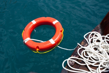 barrier rope: Safe water support aid circle with rope  Rescue red life buoy on wooden background of ship or boat  Helpful object