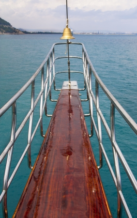Ocean liner or sea yacht nose showing direction. Bell on cruise boat. Travel background. photo