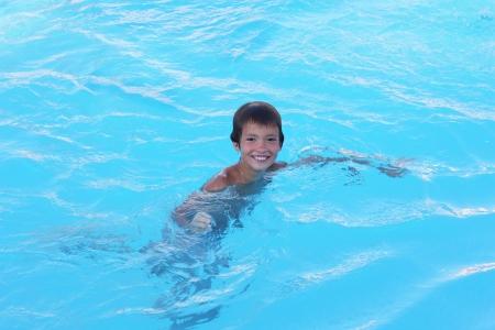 Chico Ni�o feliz en el deporte juega con una sonrisa en la piscina en un agua azul. photo