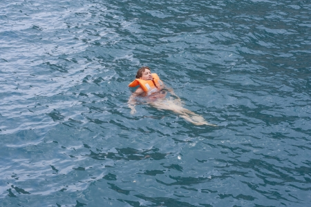 lifejacket: Woman in orange life jacket in water after sport activity. Rescue vintage lifevest object for safe sailing as heathcare element for people. Stock Photo
